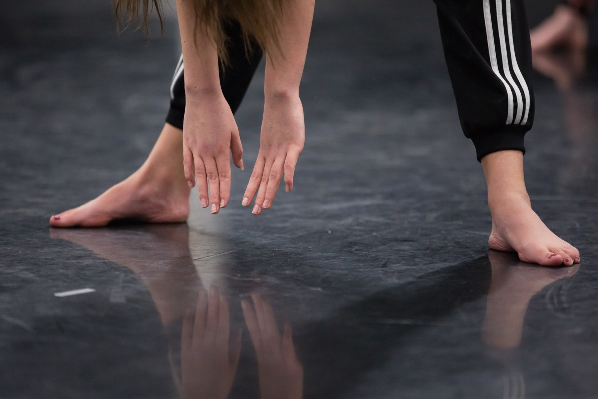A dancers hands stretched down between their feet.