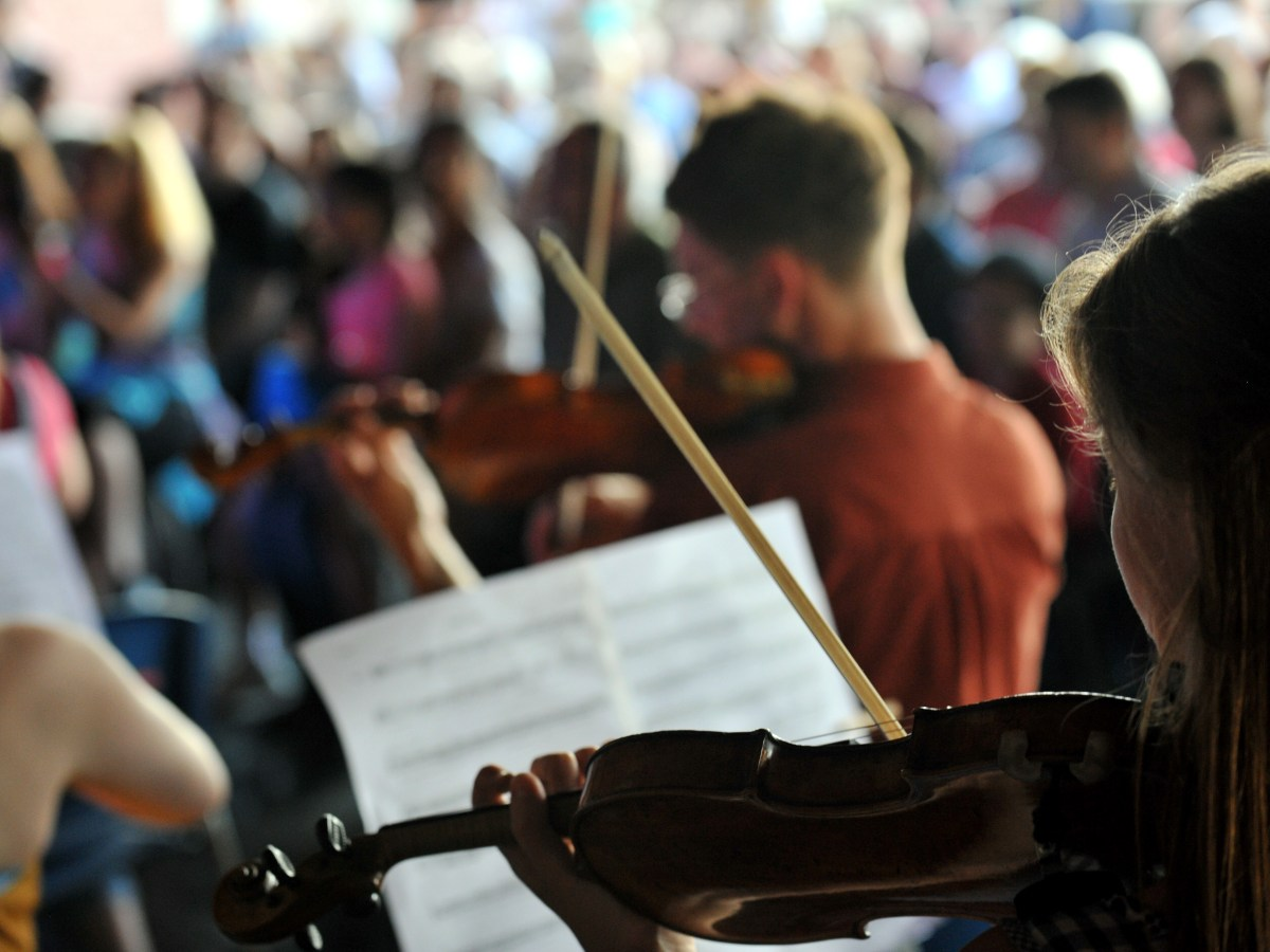 A young person playing violin in an orchestra with their sheet music in front of them.