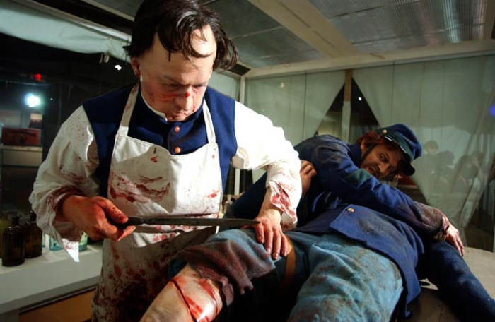 An amputation scene in a field hospital tent portrays an orderly holding a soldier in place while a surgeon works on his gangrene-blackened leg.