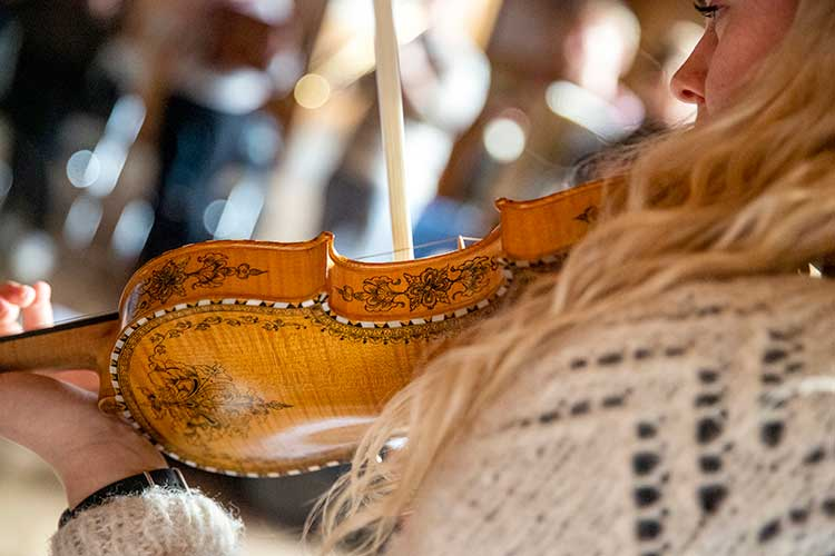 Hardanger fiddle being played, seen from behind with focus on distinctive intricate rosings and inlay