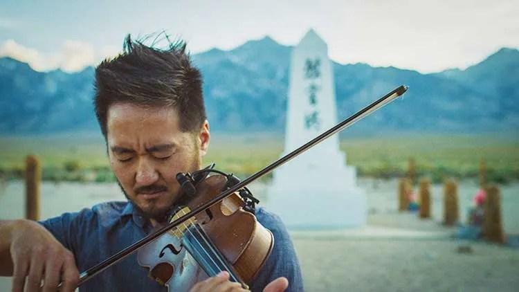 Kaoru Ishibashi, aka Kishi Bashi, playing violin outdoors