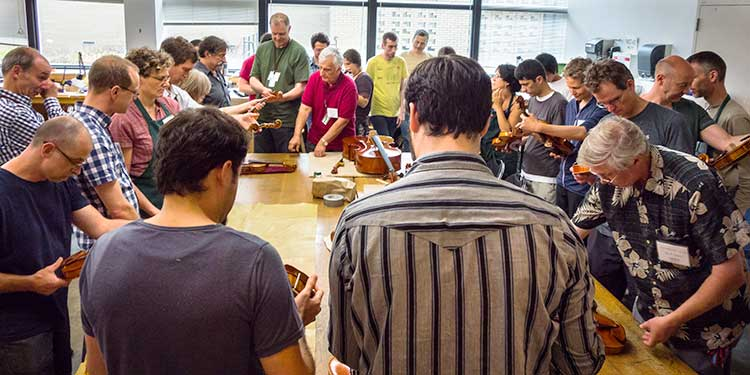 People gathered around a table at the Oberlin Violin Makers Workshop