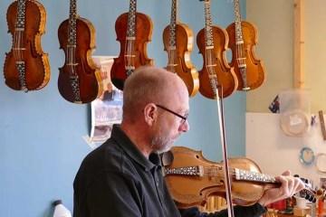 Hardanger fiddle maker Sigvald Rørlien holding a Hardanger fiddle
