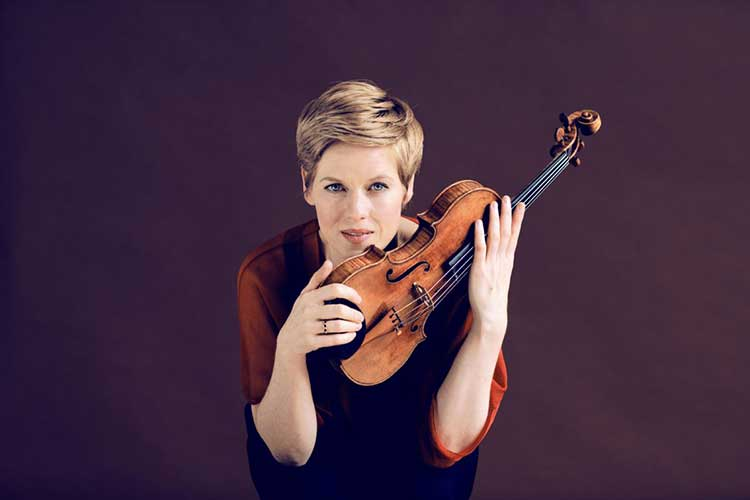 Violinist Isabelle Faust holding her instrument against a purple background