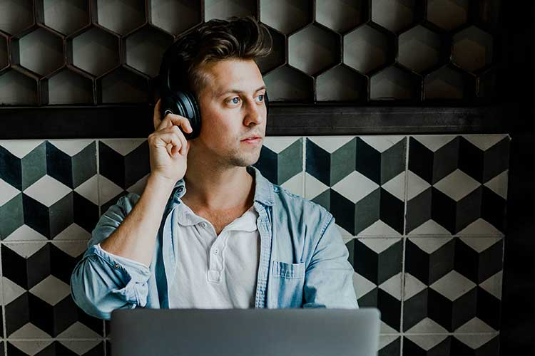 a man listening to music with headphones against a soundproof wall