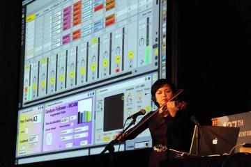 Mari Kimura plays violin with computer screen showing digital recording session
