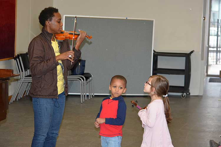 Lucinda Ali Landing playing violin in a classroom with two young students