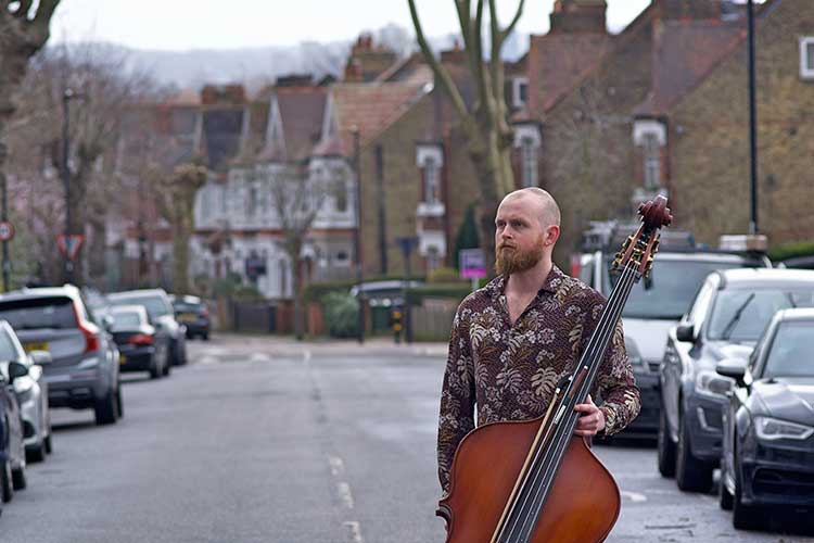 Double Bassist Toby Hughes standing with bass in a street