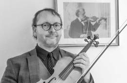 David Milsom holding a violin