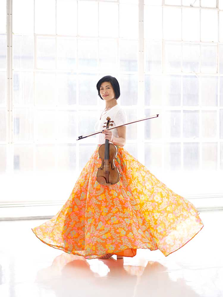 Violinist Jennifer Koh in an orange dress with violin