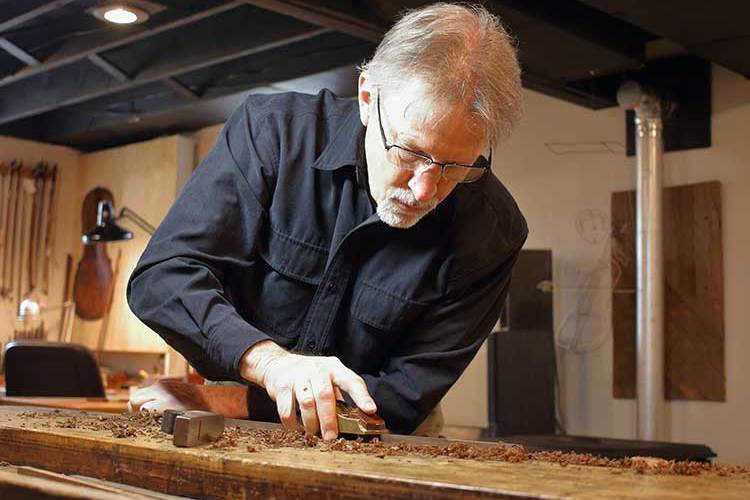 Bowmaker Richard Riggall planing a stick for a bow in his workshop