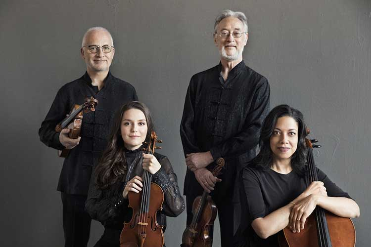 Juilliard String Quartet poses with their instruments against a gray backdrop