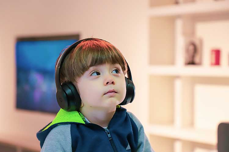 child listening to orchestra with headphones