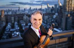 Violinist Gil Shaham holding his violin in front of a cityscape