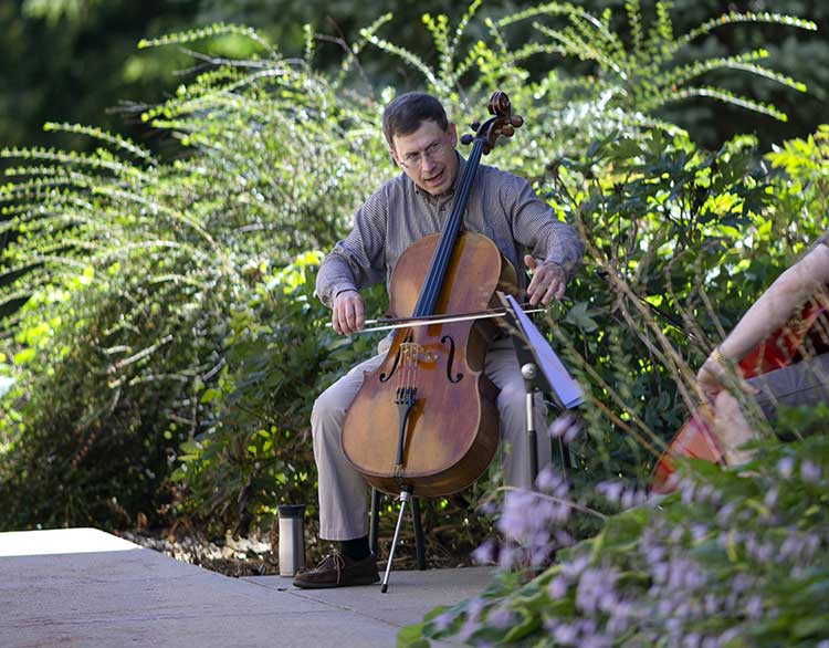 cellist Benjamin Whitcomb performing on his cello outside