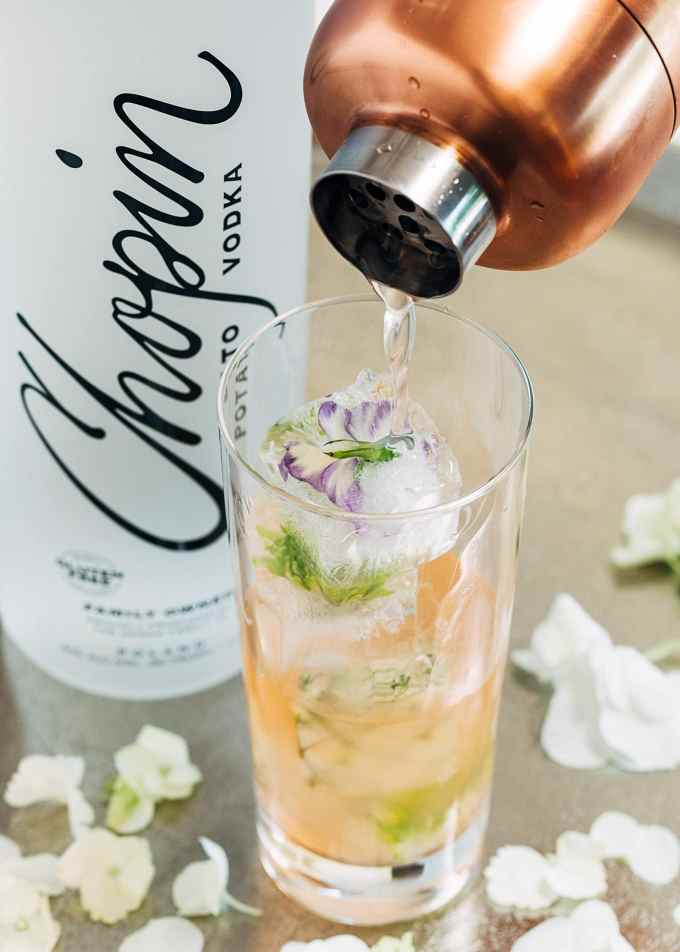 pouring vodka cocktail into a glass with flower ice cubes