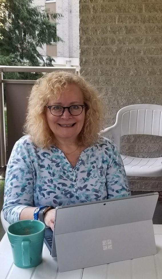 Image of Stephanie Mensh working on laptop on balcony