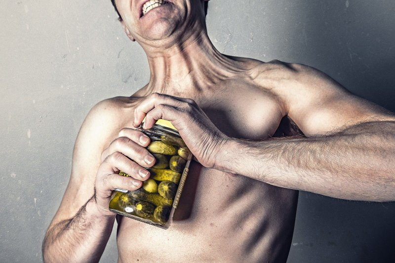 Man using grip strength to try to open jar