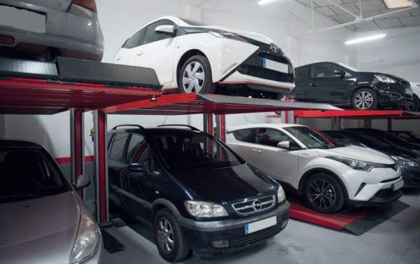Row of car lifts with cars on top and beneath