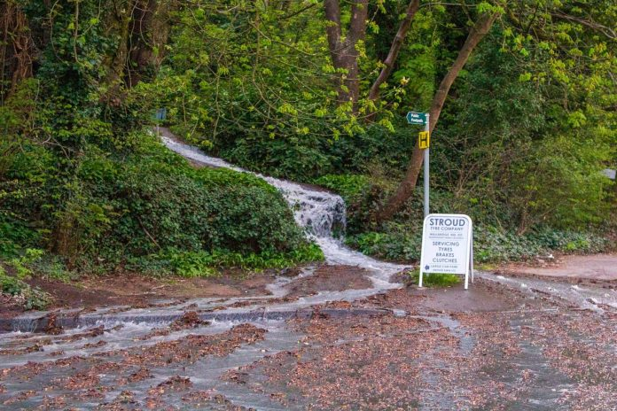 Water from the burst pipe on the Stroud to Dudbridge cycle track cascading down towards Bath Road