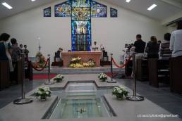 The baptismal font (foreground) and stained glass (background) in the church.