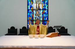 Fr Cosmas Lee raising the chalice and host during Mass.