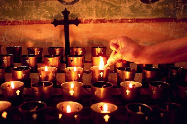 Worshiper Lighting Votive Candle on Altar