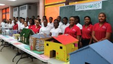 Students stand behind their green homes at the John H. Woodson Junior High School Science Laboratory.