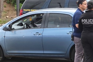 A bullet-riddled Toyota Yaris sits in the Ninky Center intersection after Thursday's shooting.