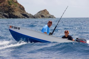 A pair of anglers make their way through the waves.