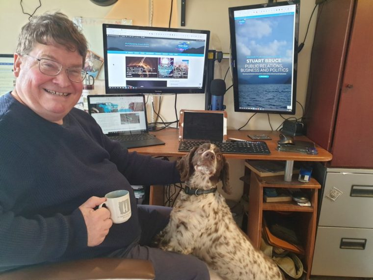 Stuart Bruce working from home with three monitors photo