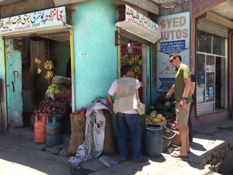 Garrett and the team chef buying fruit at a local store in Skardu
