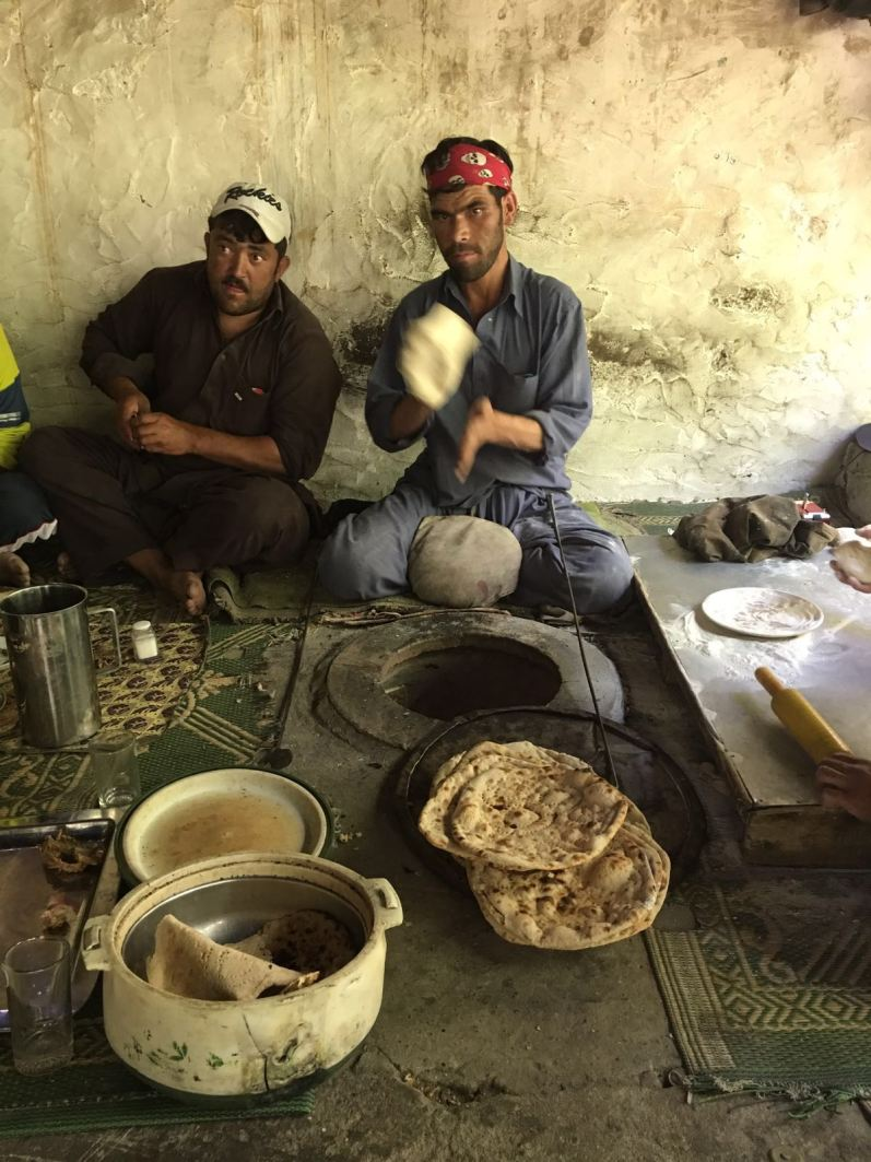 A couple of men making chapatti. The chapatti oven is the hole in the middle of the floor. This is a staple for the Pakistani people in this area.