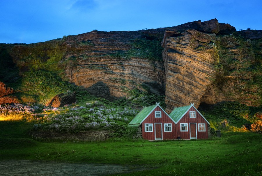 Farmhouse and Roosting Birds at DuskI only got to stay in this magical place for one night.If you're really into birds, then you may notice a thing or two about this photo.  Iceland is known for many species of birds, and you can see a bunch of them roosting back in the cliff there.- Trey RatcliffRead more here at the Stuck in Customs blog.