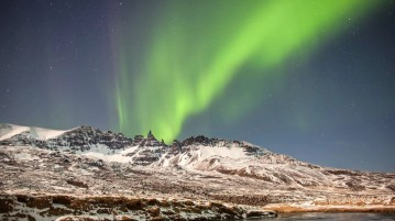 The northern lights glow and dance above the picturesque Hraundrangar peaks in the north of Iceland