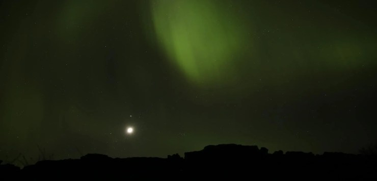 The northern lights and the moon above Thingvellir in Iceland.