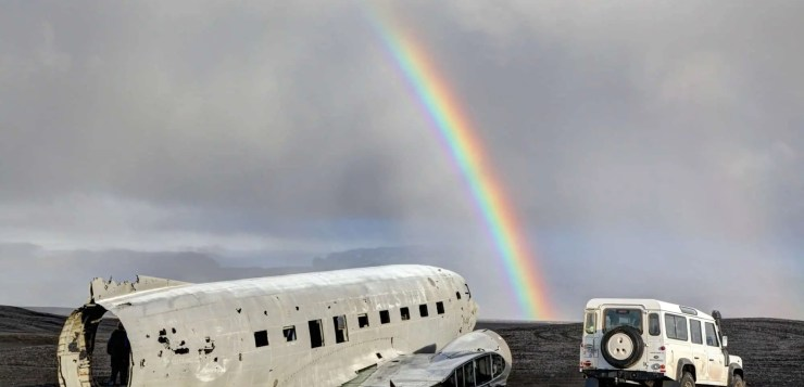 Epic Iceland Land Rover Defender Road Trip - Journey of a lifetime. Rainbow over Isey6 and the DC3 wreck at Solheimasandur.