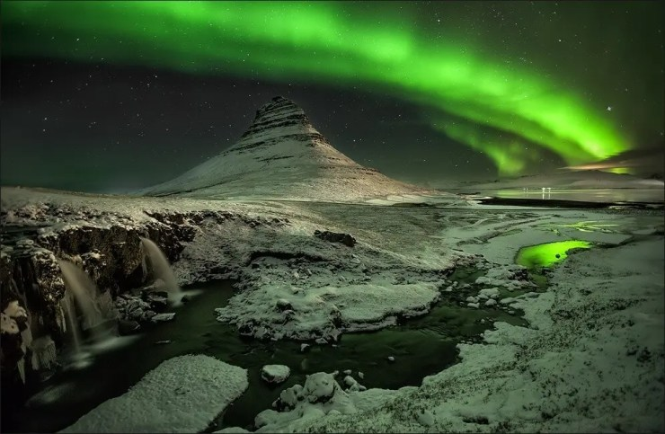 Mount Kirkjufell illuminated by northern lights - photo by Martin Schulz