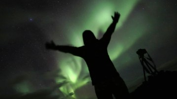 The author Nancy Claus enchanted by the Icelandic northern lights.