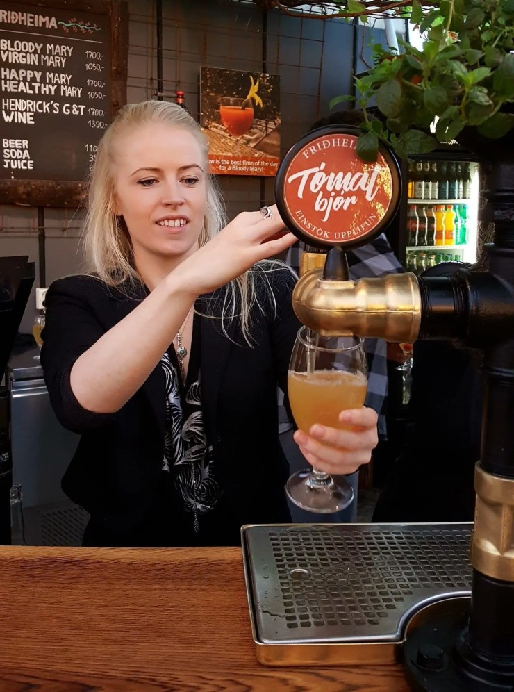 A woman pours tomato beer at Friðheimar restaurant which is on the Golden Circle in Iceland.