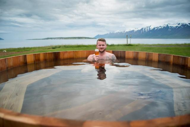 Man in a hot tub with a beer at the beer spa in Iceland.