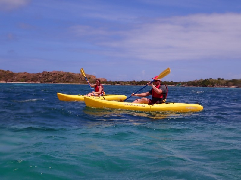A man and woman kayaking in yellow boats in St. Thomas, USVI.