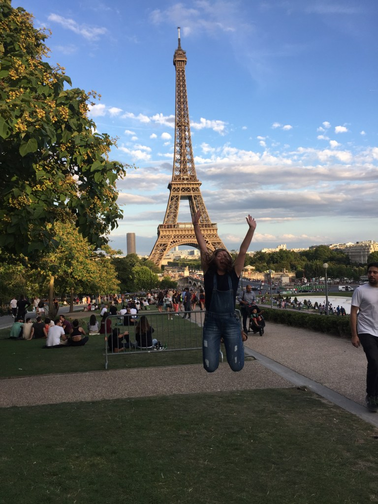 Girl jumping in front of the Eiffel Tower on a bluebird day. EF Ultimate Break made it possible to see this.