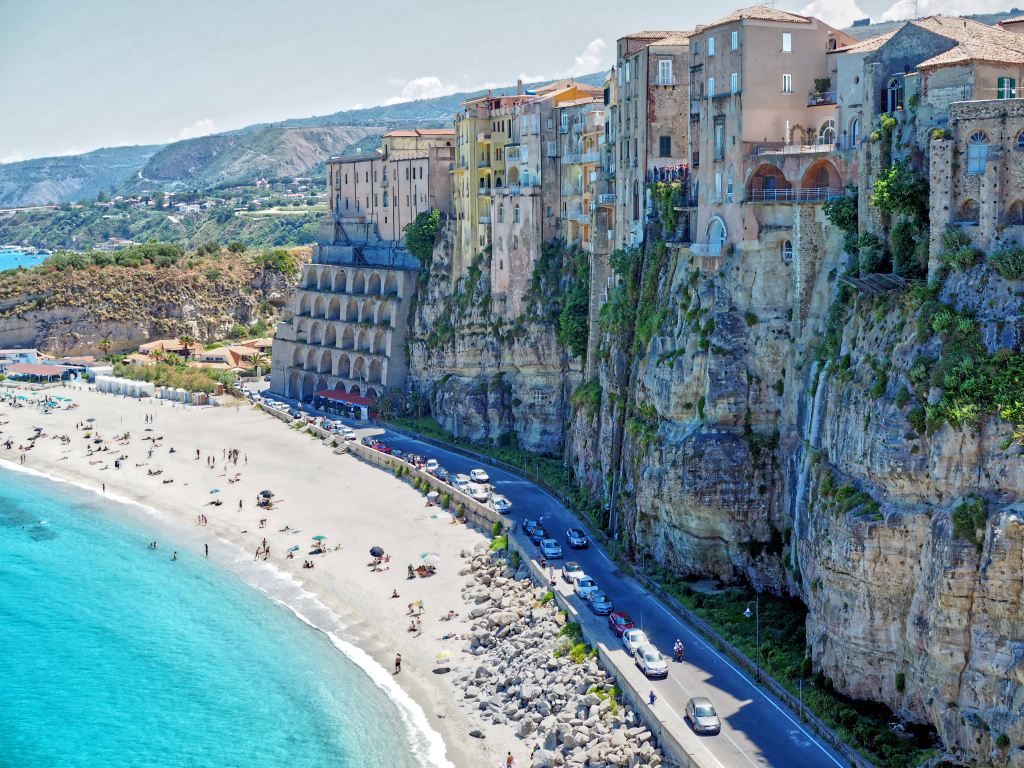 Buildings set up high on a cliff side with a beach down below. Plan a dream vacation and you could be staying here.