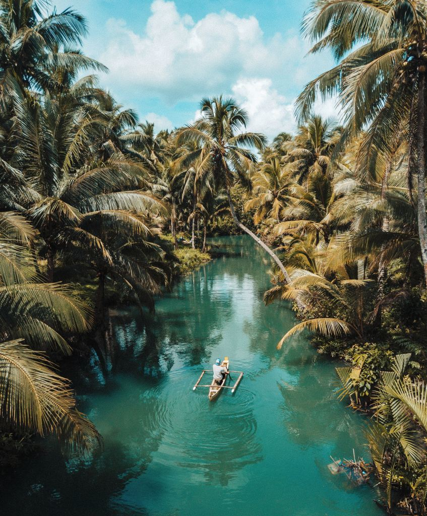 A man canoeing down a pale blue river with lush jungle surrounding him. Plan a dream vacation and this could be you.