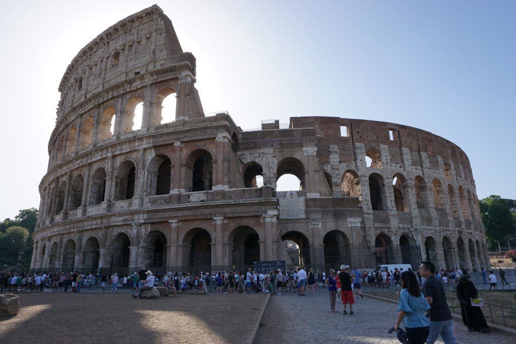 The gorgeous Colosseum with the sun rising behind it. This stop is a must on the what to do in Rome guide.