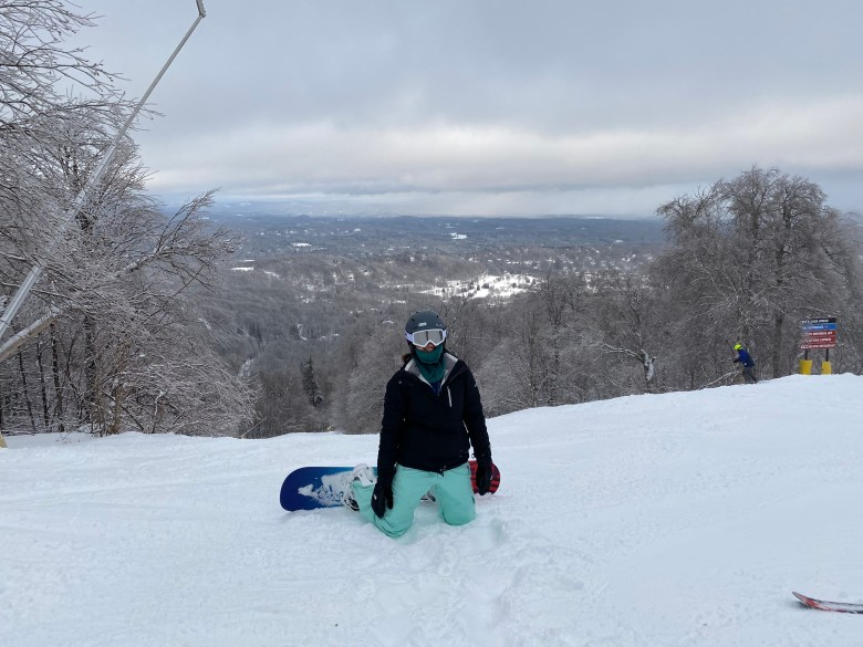 Girl on a snowboard on top of a mountain. Save money for travel so you can experience this.