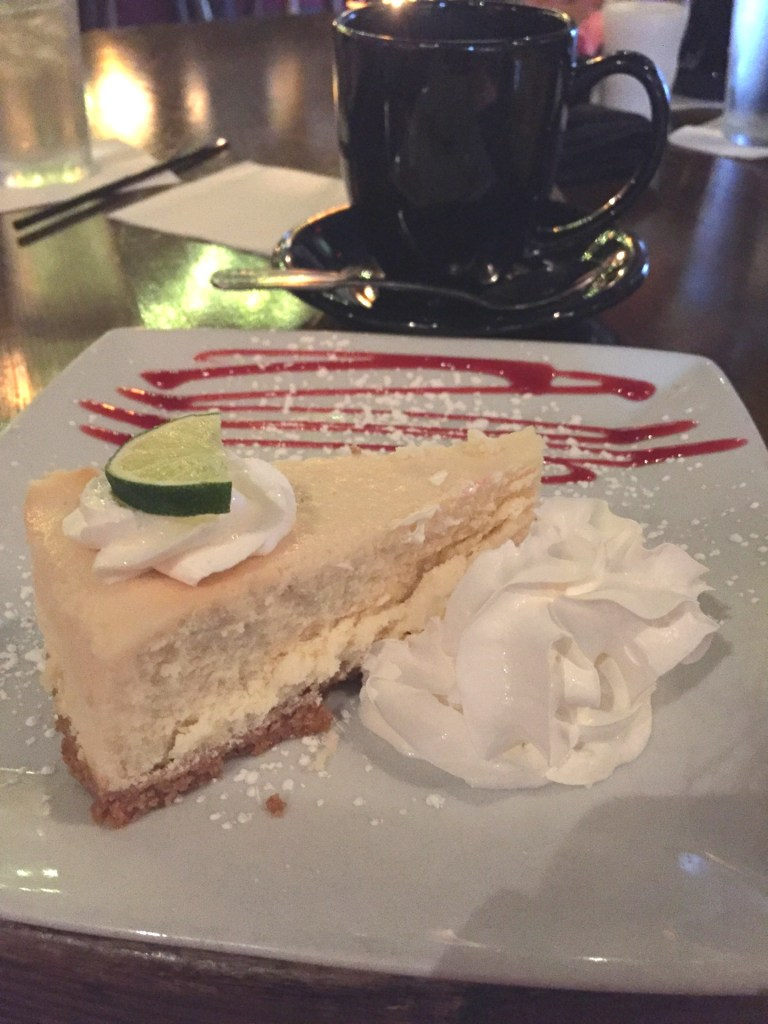 Key lime cheesecake with whipped cream and coffee in the background. Where to eat in Charleston.