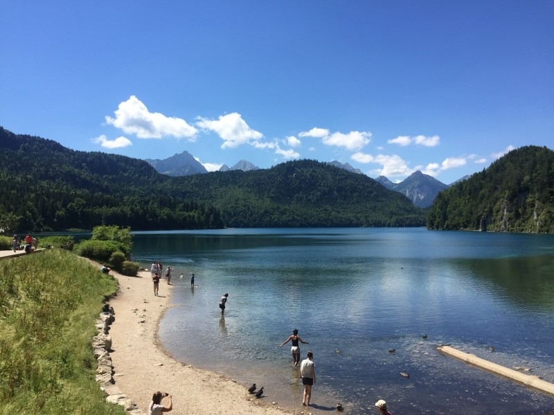 A lake with people wading in it and towering mountains in the background. The beautiful landscape is one of the major reasons to visit Bavaria, Germany.