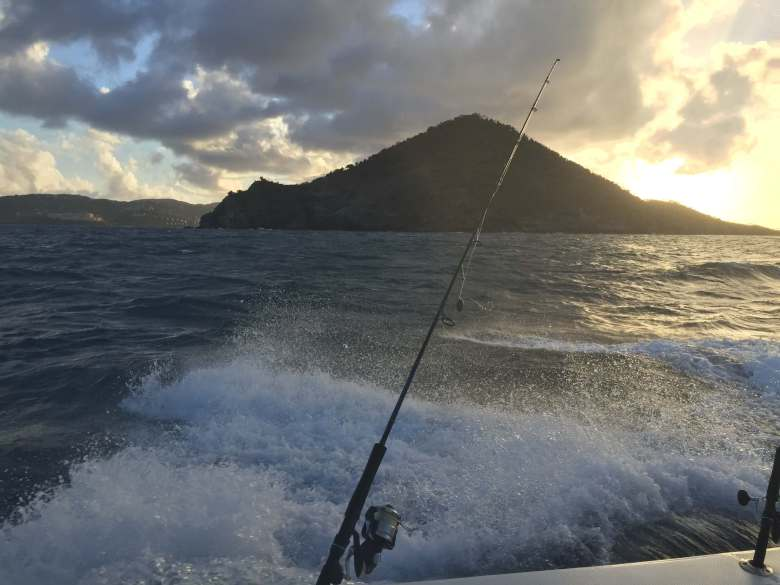 Sunset behind a mountain with a fishing rod in front of the waves.